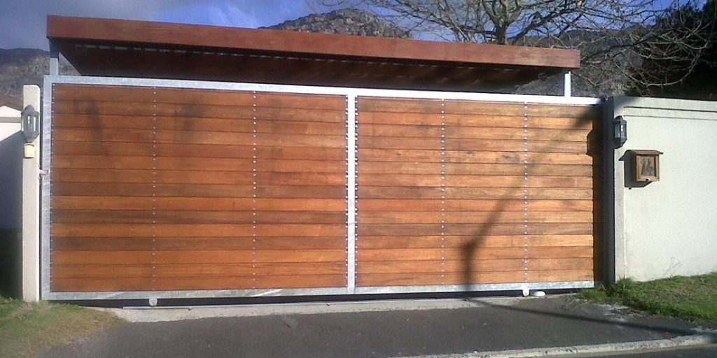 Tongue & groove horizontal slatted meranti sliding gate installed in front of carport